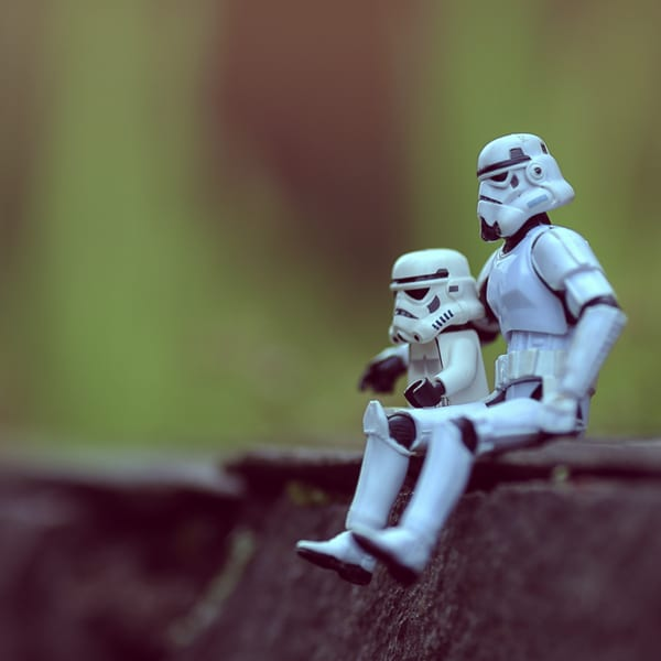 Photo of a Star Wars stormtrooper action figure and Stormtrooper minifigure sitting outdoors, like father and son (close up) • Earnest Labs